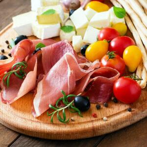 Tabla de aperitivos con jamón, queso, tomates cherry y grissini